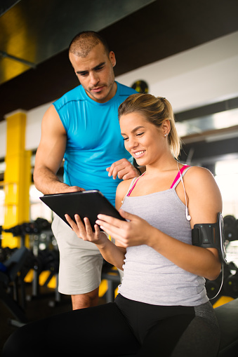 860045834 istock photo Young woman discussing workout progress with fitness instructor 624912652