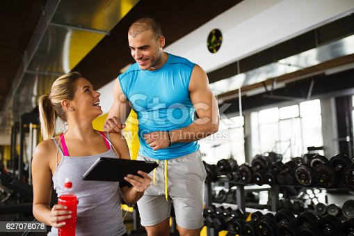 860045834istockphoto Young woman discussing workout progress with fitness instructor 627076078
