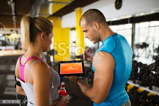 istock Young woman discussing workout progress with fitness instructor 627076152