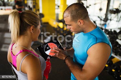 860045834istockphoto Young woman discussing workout progress with fitness instructor 627076242