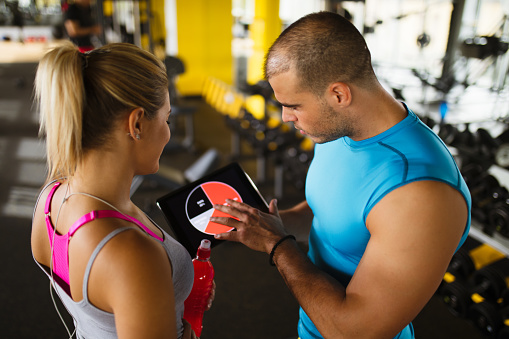 860045834 istock photo Young woman discussing workout progress with fitness instructor 627076242