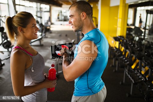 860045834istockphoto Young woman discussing workout progress with fitness instructor 627076276