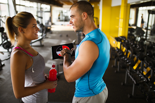 860045834 istock photo Young woman discussing workout progress with fitness instructor 627076276