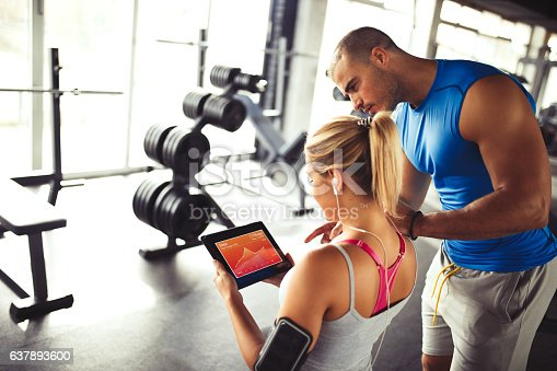 860045834istockphoto Young woman discussing workout progress with fitness instructor 637893600