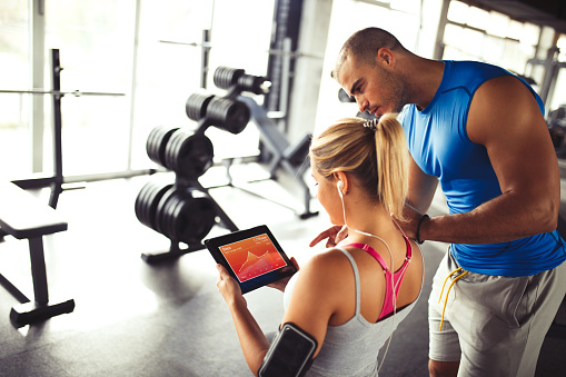 860045834 istock photo Young woman discussing workout progress with fitness instructor 637893600