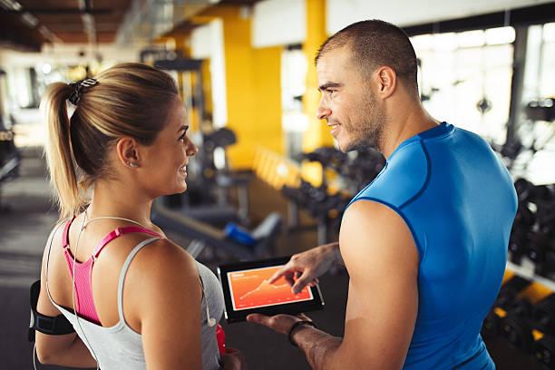 young woman discussing workout progress with fitness instructor - trainingsplan frauen stock-fotos und bilder