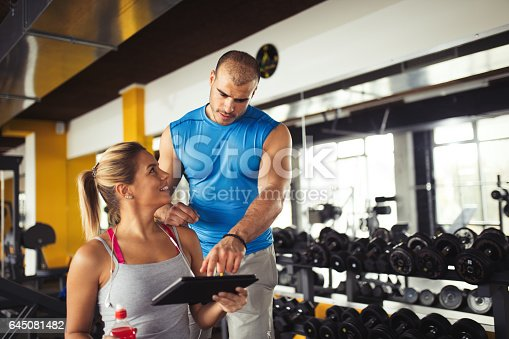 860045834istockphoto Young woman discussing workout progress with fitness instructor 645081482