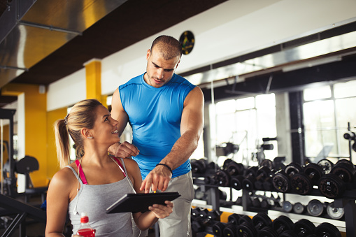 860045834 istock photo Young woman discussing workout progress with fitness instructor 645081482