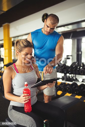 860045834istockphoto Young woman discussing workout progress with fitness instructor 645084530