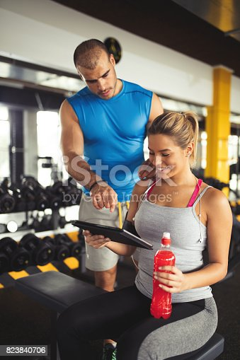 860045834istockphoto Young woman discussing workout progress with fitness instructor 823840706