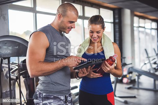 860045834istockphoto Young woman discussing workout progress with fitness instructor 860035974