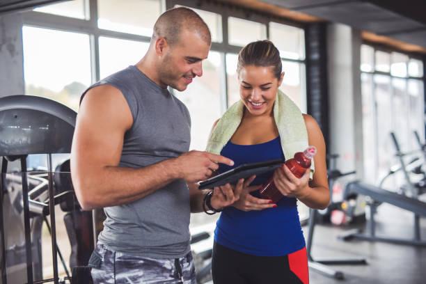 junge frau mit fitness-instruktor training fortschritte zu diskutieren - trainingsplan frauen stock-fotos und bilder