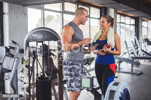 istock Young woman discussing workout progress with fitness instructor 860045834
