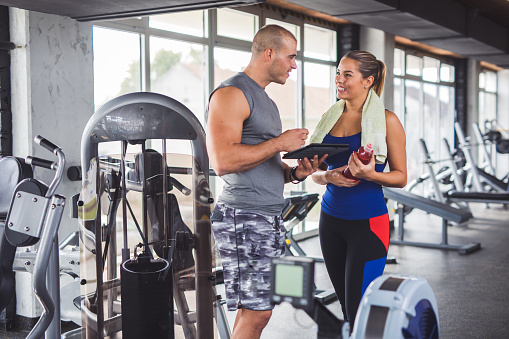 860045834 istock photo Young woman discussing workout progress with fitness instructor 860045834