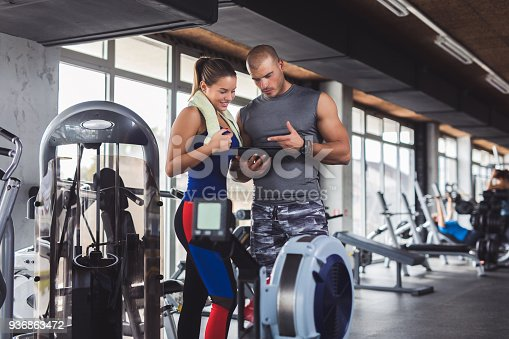 860045834istockphoto Young woman discussing workout progress with fitness instructor 936863472
