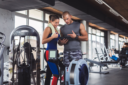 860045834 istock photo Young woman discussing workout progress with fitness instructor 936863472
