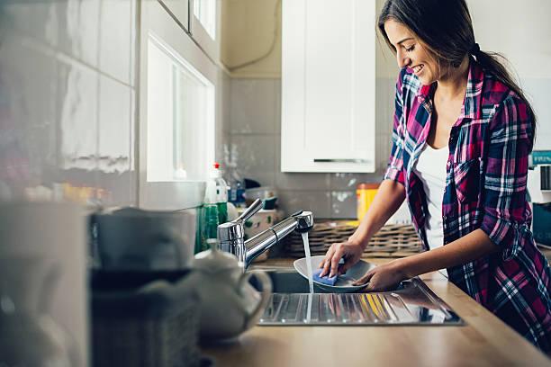 Young woman dish washing foto
