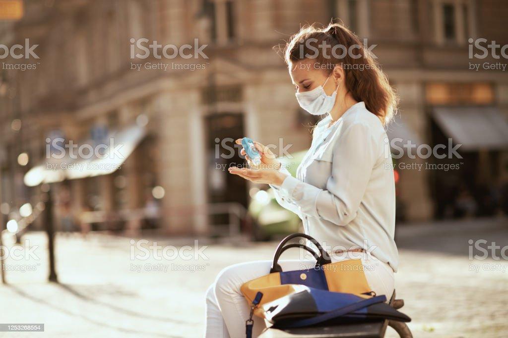 jonge vrouw die handen met ontsmettingsmiddel in openlucht in stad ontsmet - Royalty-free Ademhalingsbeschermingsmasker Stockfoto