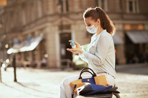 Jonge Vrouw Die Handen Met Ontsmettingsmiddel In Openlucht In Stad Ontsmet Stockfoto en meer beelden van Ademhalingsbeschermingsmasker