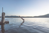 A young ethnic woman in bikini dives in the lake from the diving board on the pier. It is dusk. On the other side of the lake are houses, forest, and a mountain range. The moon is visible in the evening sky.