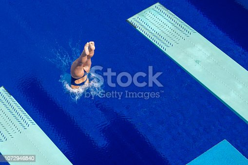 Young woman diving from diving board in swimming pool.