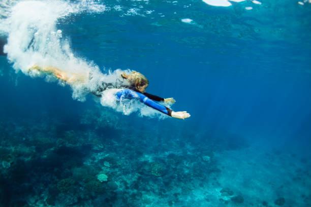 young woman diving underwater - nuoto mare foto e immagini stock
