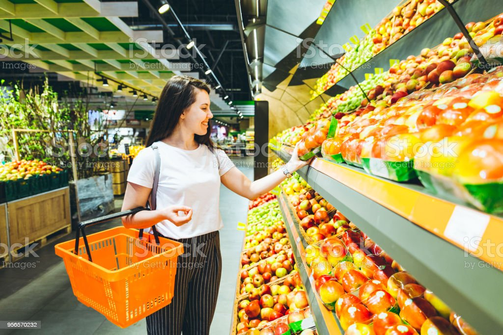young woman do shopping in supermarket. choosing apples in store stock photo
