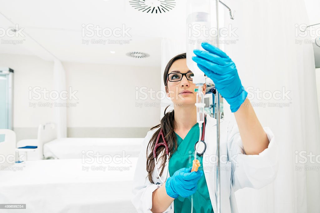 Young woman doctor anesthesiologist dressed in green gown, puts stock photo