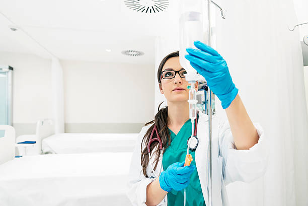 Young woman doctor anesthesiologist dressed in green gown, puts Young woman doctor anesthesiologist dressed in green gown, puts the dropper in hospital room iv drip stock pictures, royalty-free photos & images