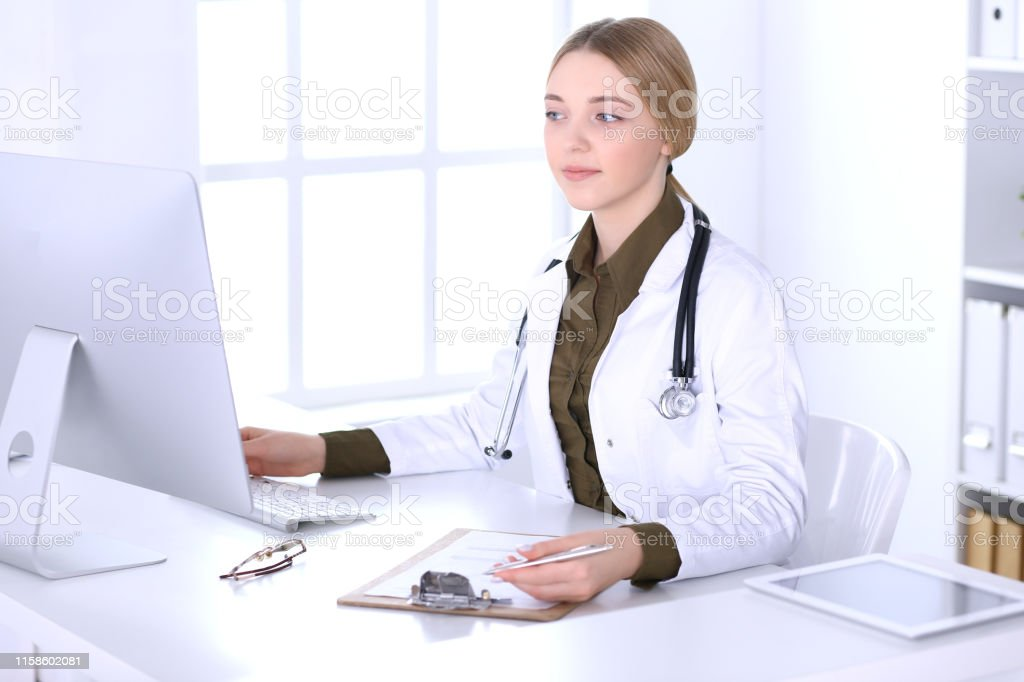 Young woman doctor at work in hospital looking at desktop pc monitor....