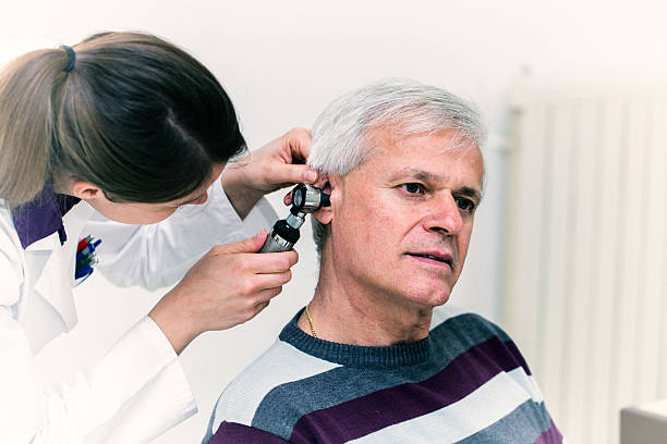 Young woman doctor checking patients ear with otoscope stock photo