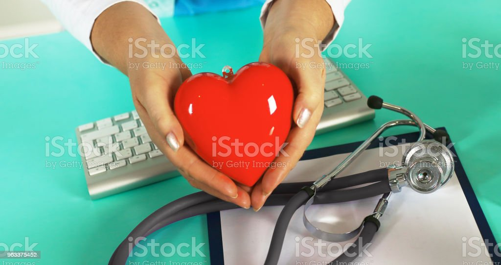 Young woman doctor holding a red heart, in office - Zbiór zdjęć royalty-free (Białoruś)