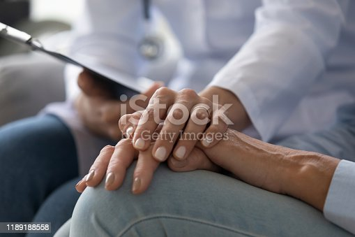 1021670950istockphoto Young woman doctor holding hand of senior grandmother patient, closeup 1189188558