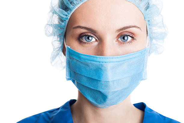 young woman doctor in cap and face mask - face mask bildbanksfoton och bilder