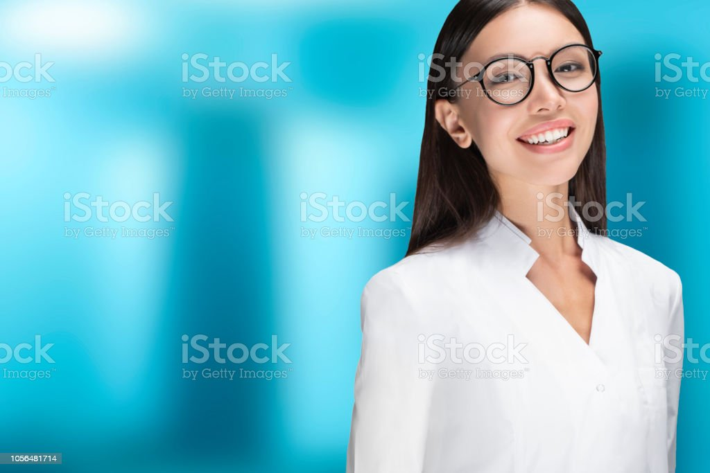 A young woman doctor smiling, standing in front of a blue background. Communicate about health care, medical, technology stock photo