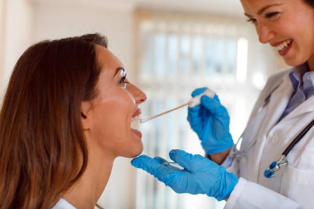 Junge Frau Doktor nimmt einen Abstrich von der Kehle – Foto