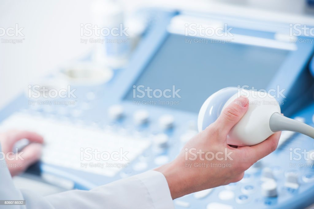 young woman doctor's hands close up preparing for an ultrasound device scan stock photo