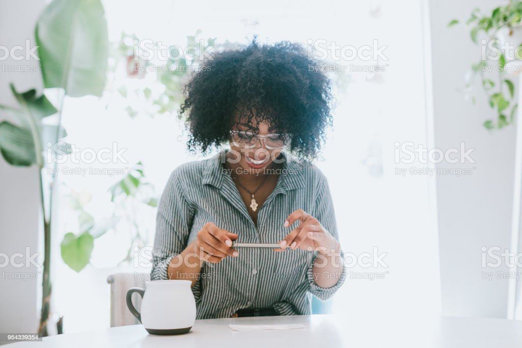 A Young Woman Does Remote Deposit Capture of Check stock photo