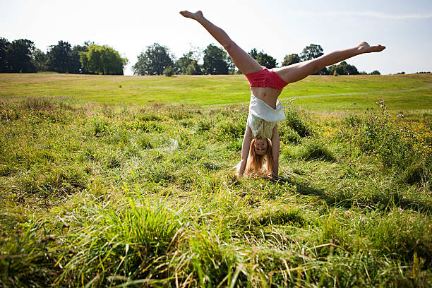 Young woman doing a handstand in a field stock photo