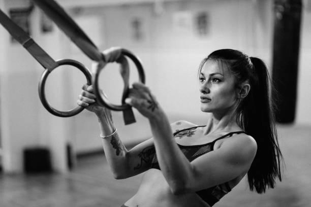 junge frau, die einen ring trainieren im fitnessstudio - gymnastik tattoo stock-fotos und bilder