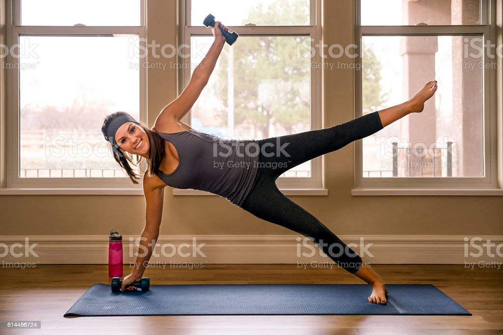 Young Woman doing a side plank with weights in Yoga stock photo