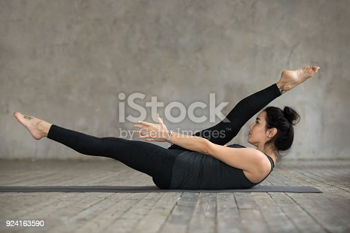 914755474 istock photo Young woman doing alternate leg stretch exercise 924163590
