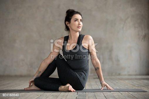 istock Young woman doing Ardha Matsyendrasana exercise 924163540