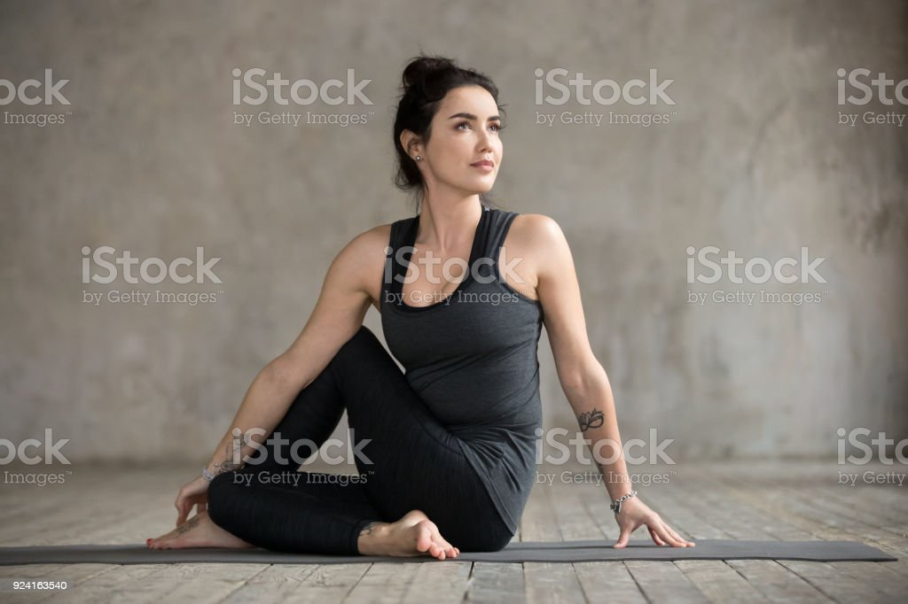 Young woman doing Ardha Matsyendrasana exercise stock photo