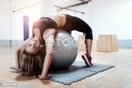 istock Young Woman Doing Backbend on Fitness Ball in Gym 599467906
