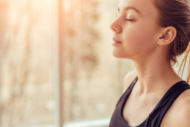 Young woman doing breathing exercise Side view of young female with closed eyes breathing deeply while doing respiration exercise during yoga session in gym wellbeing stock pictures, royalty-free photos & images