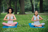 istock Young woman doing breathing exercises with her daughter 1023555220