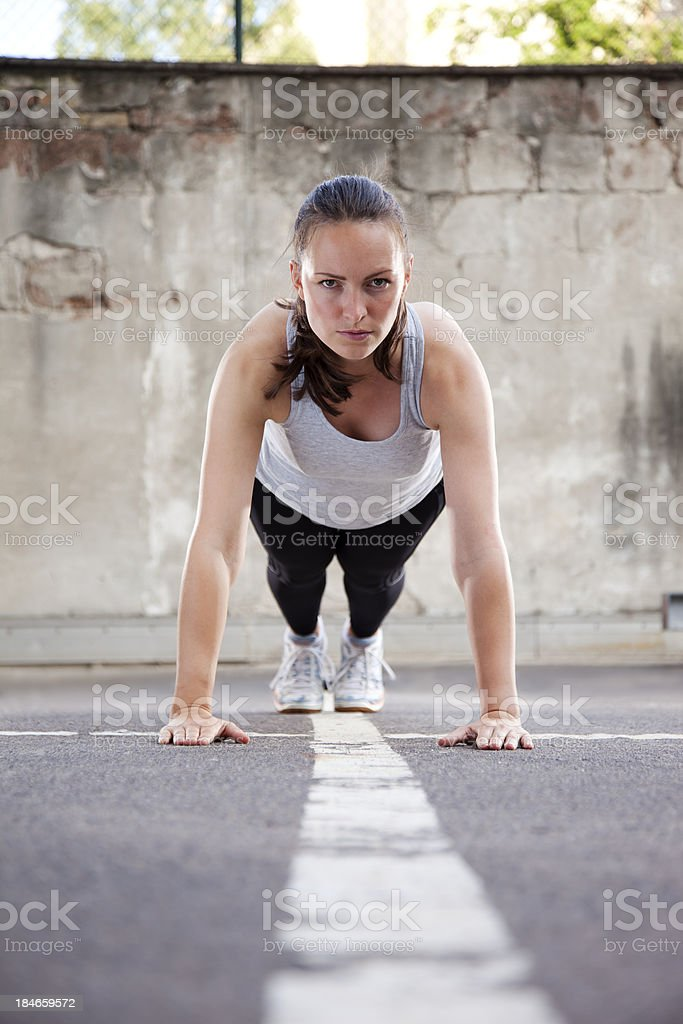 Young woman doing Burpee exercise stock photo
