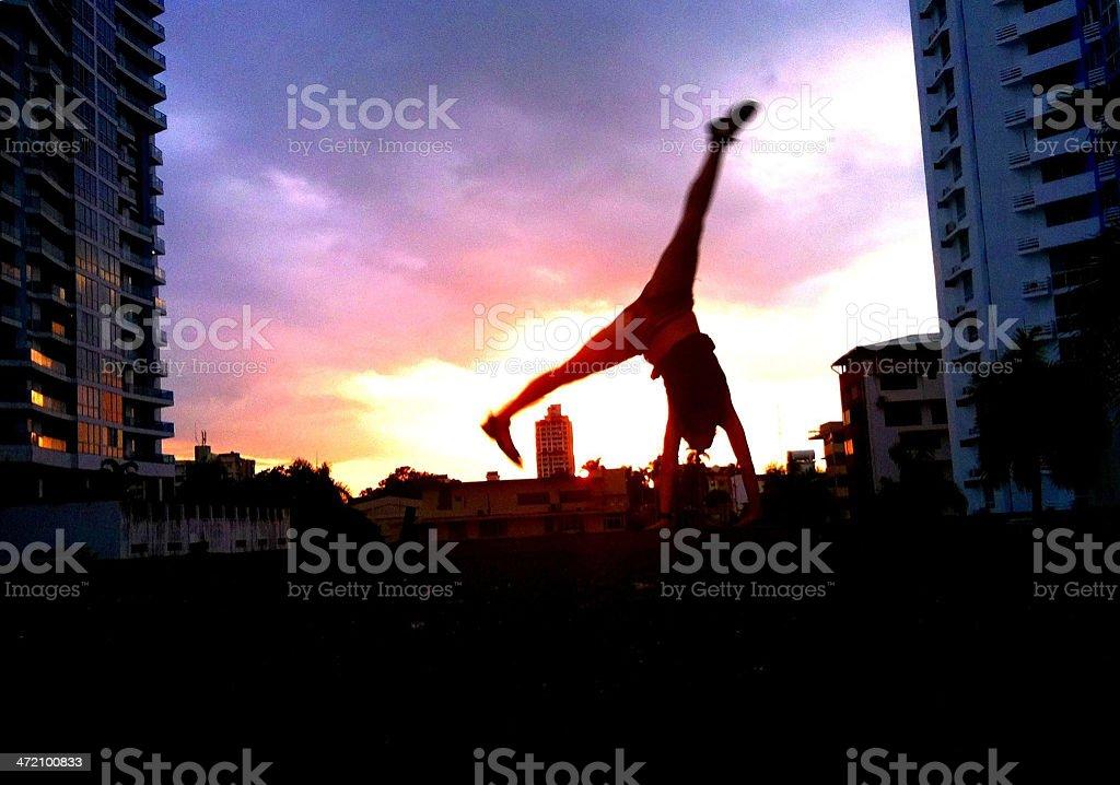 Young woman doing cartwheel at sunset stock photo