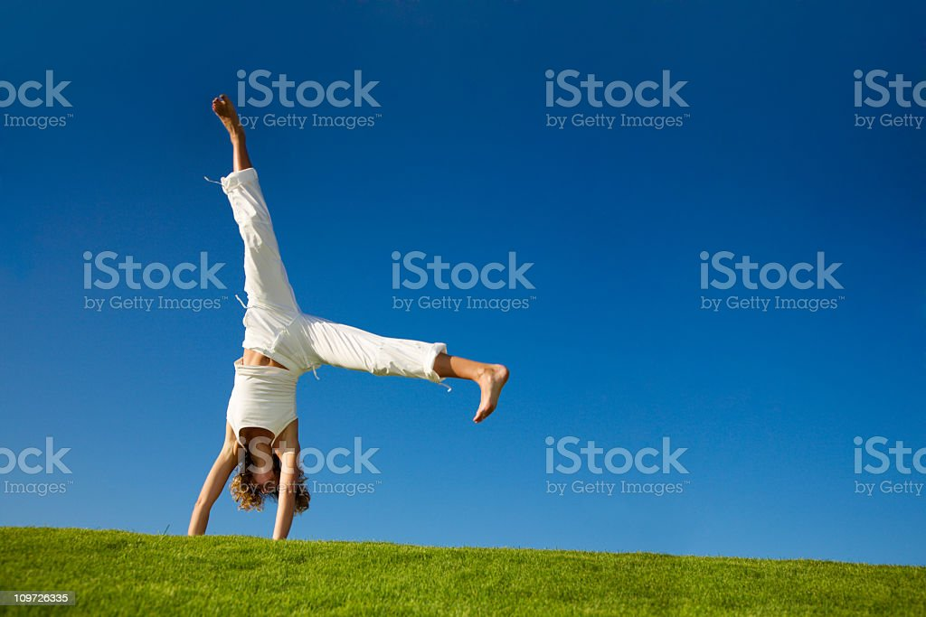 Young woman doing cartwheel in a grassy field stock photo